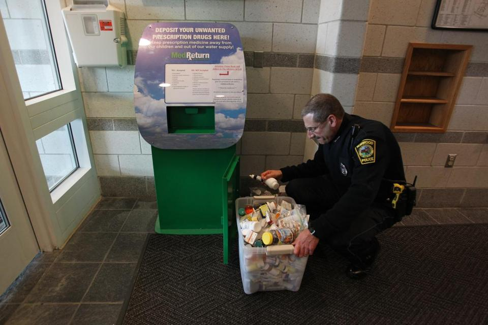 A Norwood officer empties out the drug kiosk in the police station.