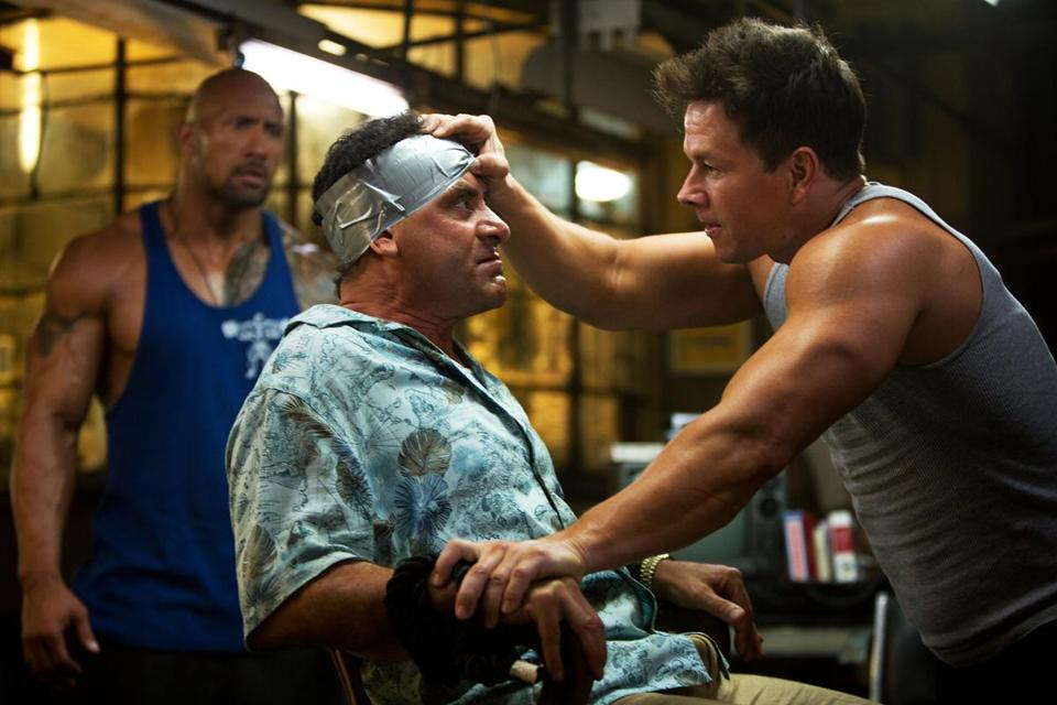 Dwayne Johnson (left) and Mark Wahlberg (right, with Tony Shalhoub) play bodybuilders who become kidnappers.