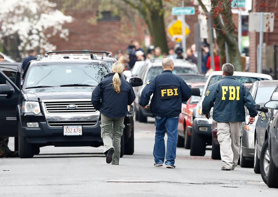 Members of the FBI, State Police, Boston Police, Cambridge Police, and other law enforcement agencies  near the home of one of the Marathon bombing suspects in Cambridge.