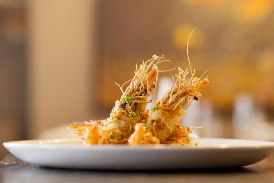 Crispy shrimp consists of two large prawns, their heads on, resting on a bed of Italian slaw.