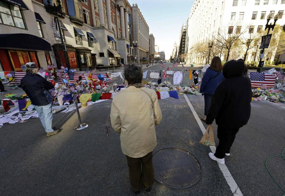 Onlookers paused at a memorial to the victims of the Boston Marathon bombings near the scene of the blasts on Boylston Street on Sunday.