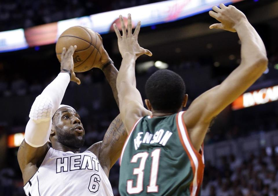 Miami's LeBron James takes aim with a jumper against Milwaukee's John Henson. The Heat took a 2-0 series lead.