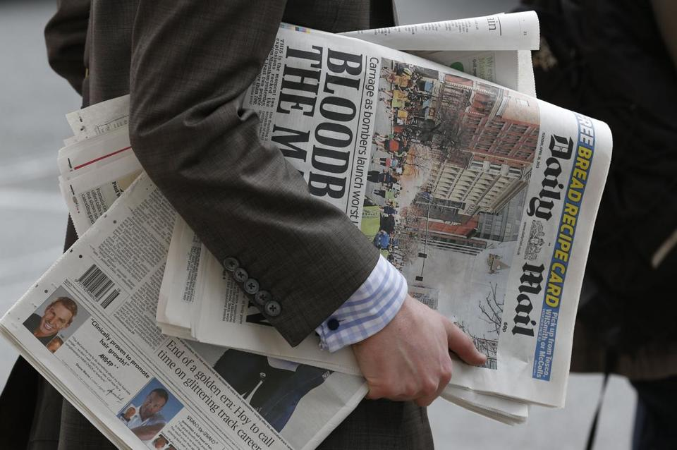 The day after the Marathon bombings, a man in London carried newspapers featuring the story.