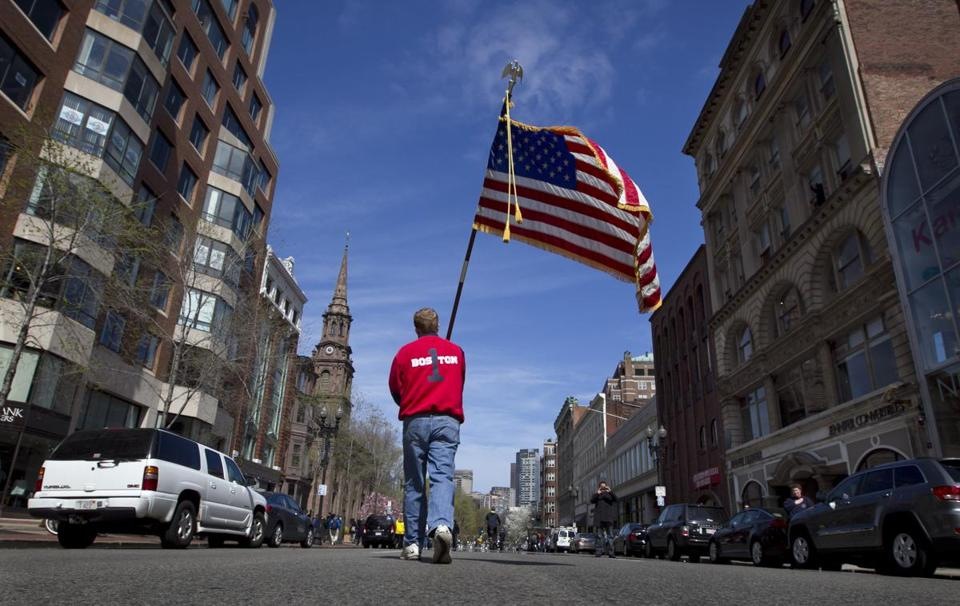 Mike Murphy, a Newton firefighter, carried an American flag down Boylston Street after observing a moment of silence last Monday.