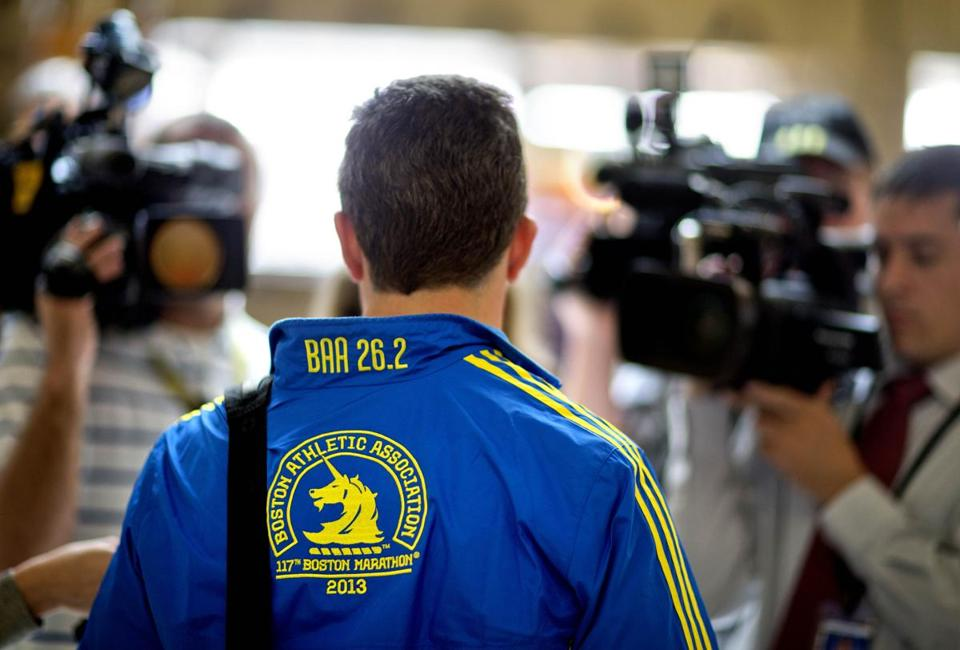 A Marathon runner on his way home was surrounded by television reporters at the Atlanta airport on April 16.