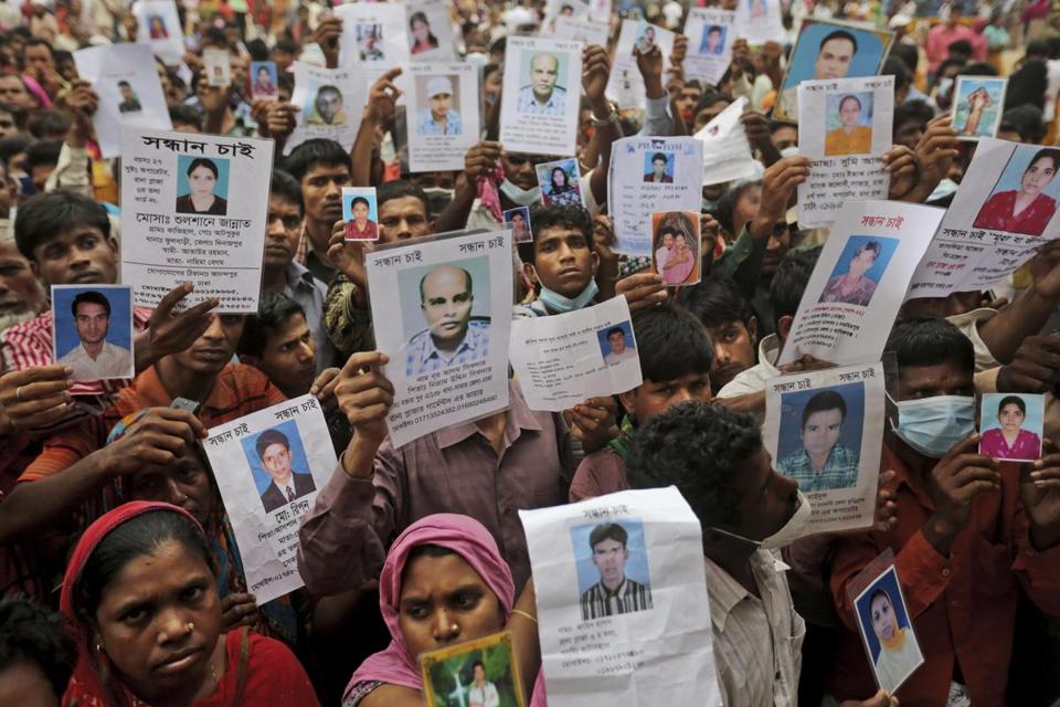 Relatives of workers missing since last Wednesday's disaster held pictures of their family members Sunday in Savar.