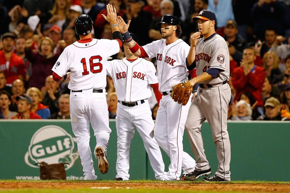 Will Middlebrooks (16) is greeted by Jarrod Saltalamacchia at the plate after both scored on Jacoby Ellsbury's double in the second inning.