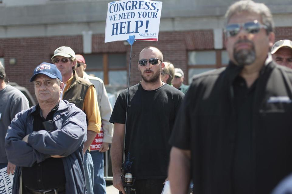 Holding a sign on a fishing rod, Nathan Hillier joined other New England fishermen during a rally at the Boston fish pier asking for relief from cuts in fish catch limits.