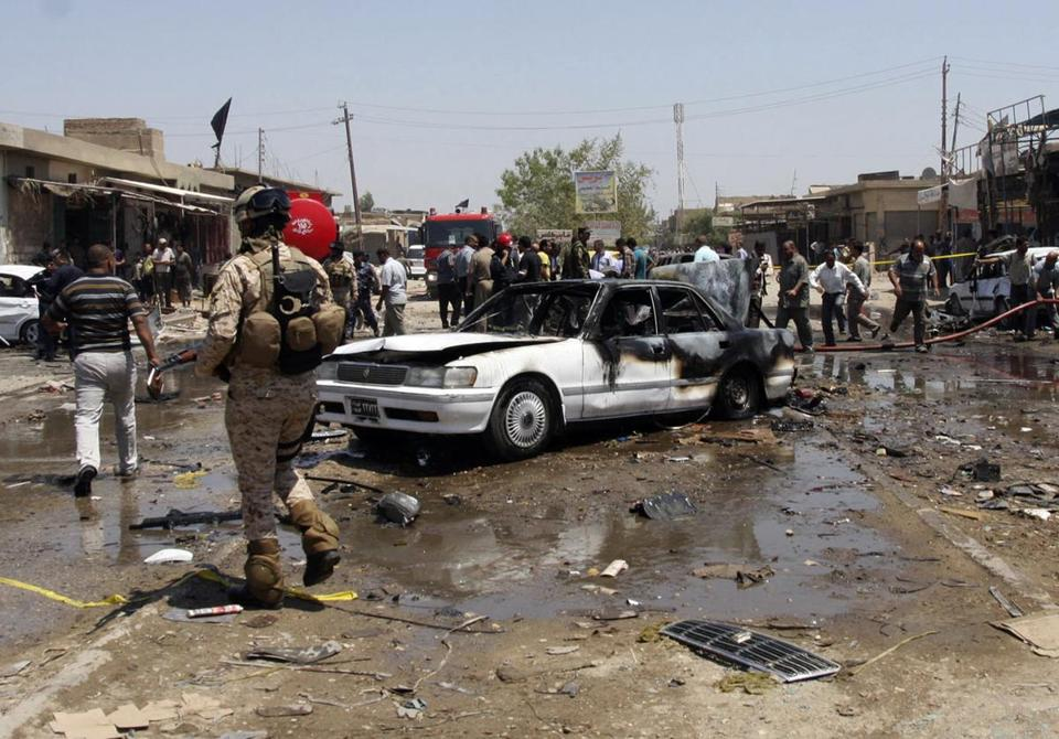 Civilians and security forces gathered at the scene of a bomb attack in the Shi'ite city of Karbala in Iraq.