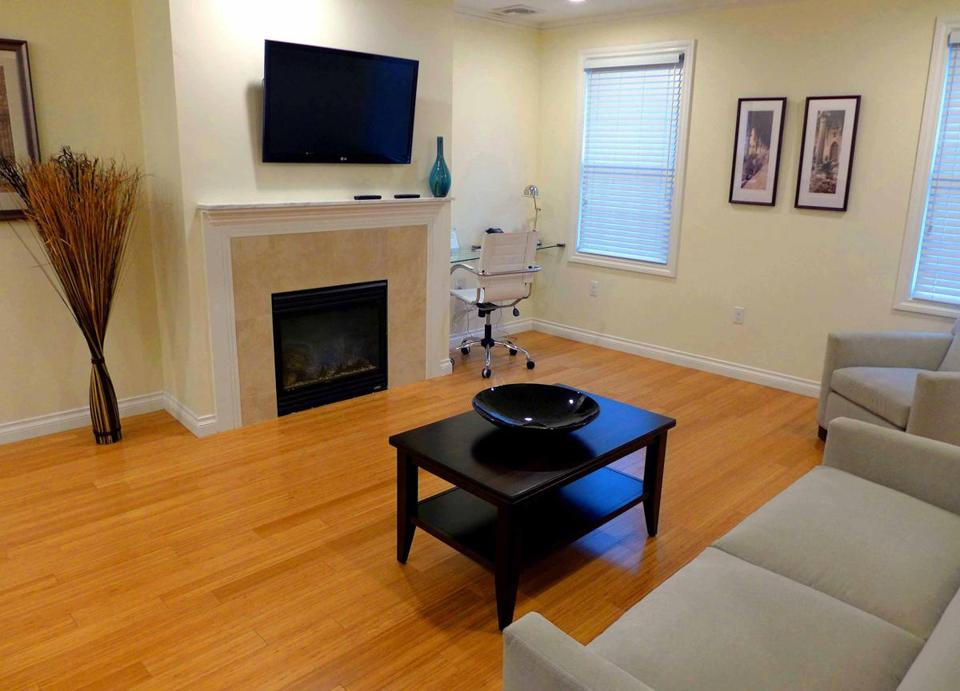 Living area in Bricco Suites room includes a fireplace, large television, and comfortable contemporary furniture.
