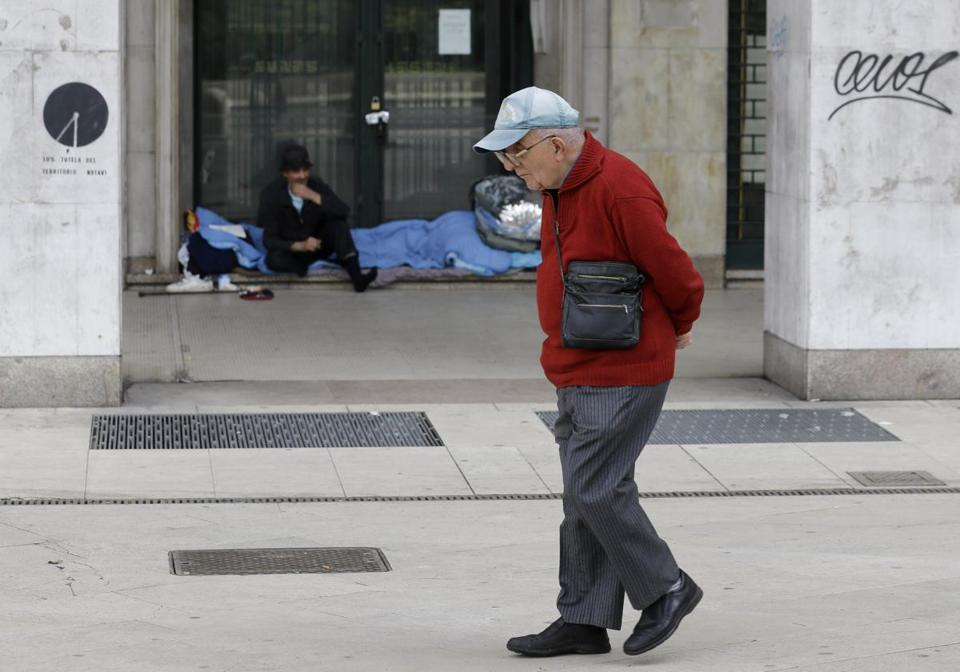 A man passed a homeless person in Milan. The Italian government has struggled to cut the nation's debt.