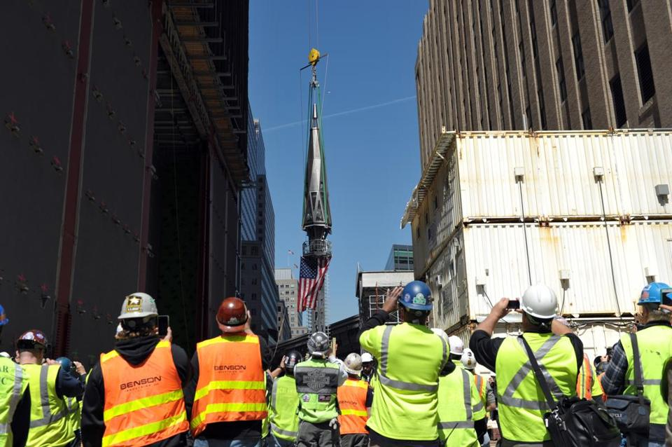 Construction workers watched as the final sections of the spire was raised to the top of One World Trade Center.
