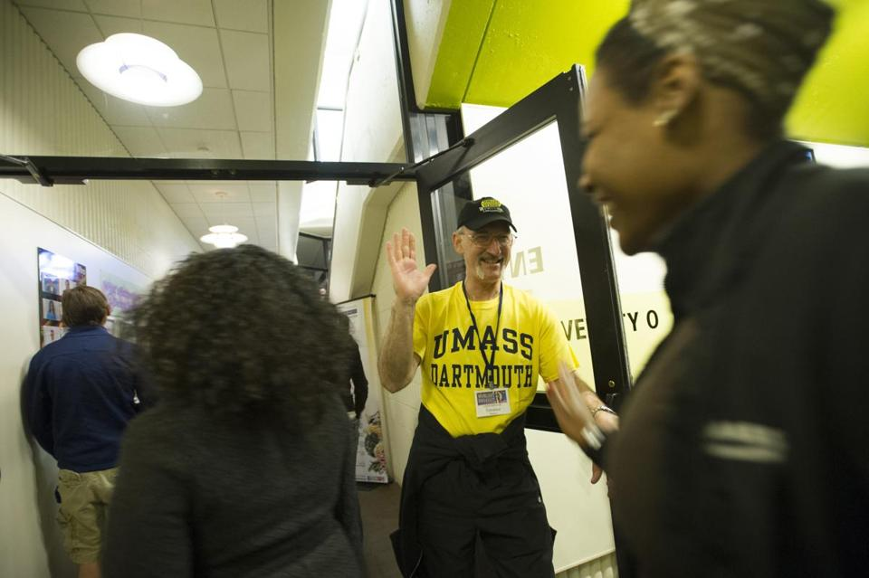 Terrance Burton, dean of library services at UMass Dartmouth, greeted students with a high-five as they arrived for the school's Moonlight Breakfast.