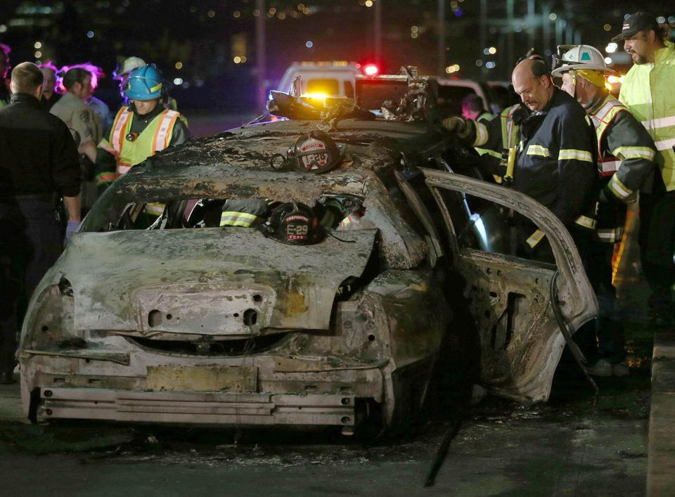 Calif. firefighters investigated the charred remains of a limousine on the San Mateo-Hayward Bridge Saturday.