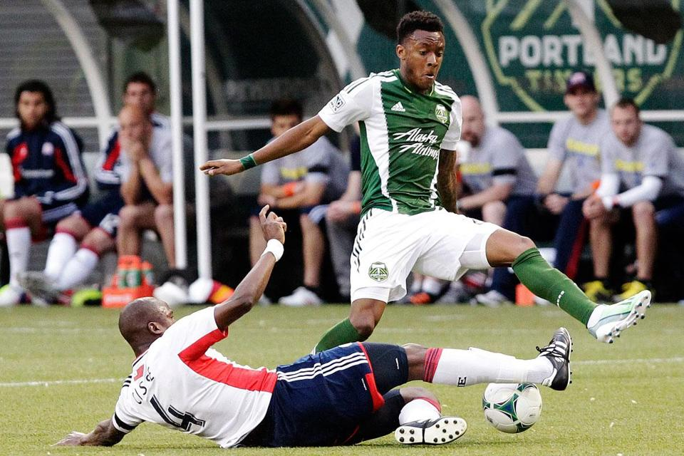 Revolution midfielder Kalifa Cisse (left) slides in to steal the ball from Timbers forward Rodney Wallace during the first half.