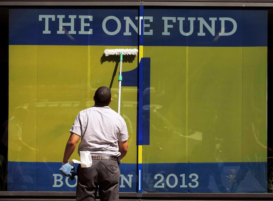 A worker in Boston cleaned a window displaying a banner for The One Fund.