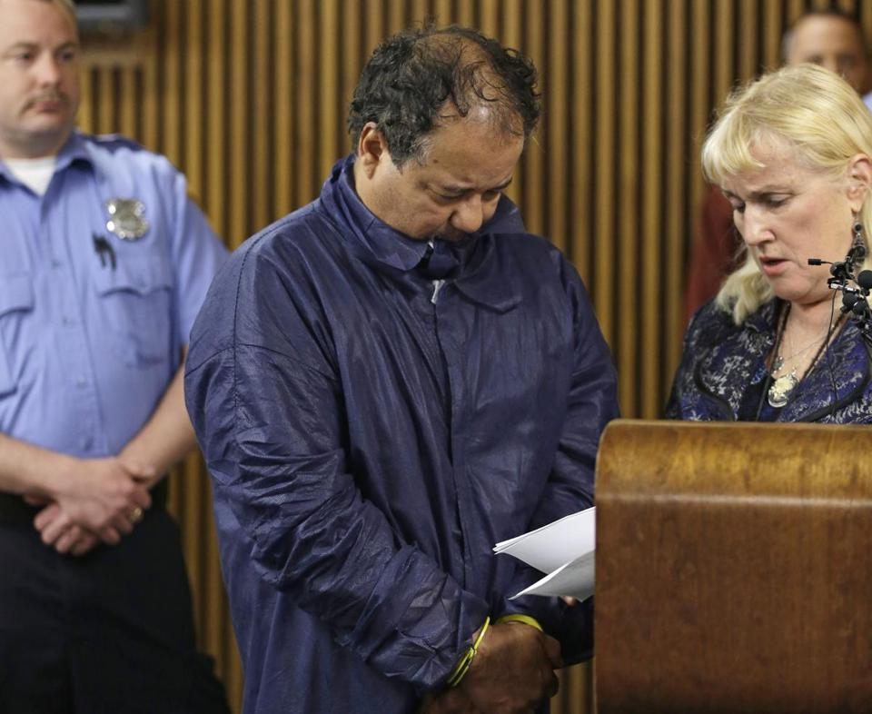 Ariel Castro tried to hide his face during his arraignment Thursday. He was assigned a lawyer, Kathleen DeMetz (right).
