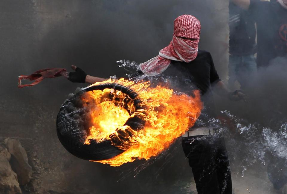 A Palestinian set fire to a tire during clashes between hundreds of Palestinians and Israeli soldiers in Betunia near the West Bank city of Ramallah.