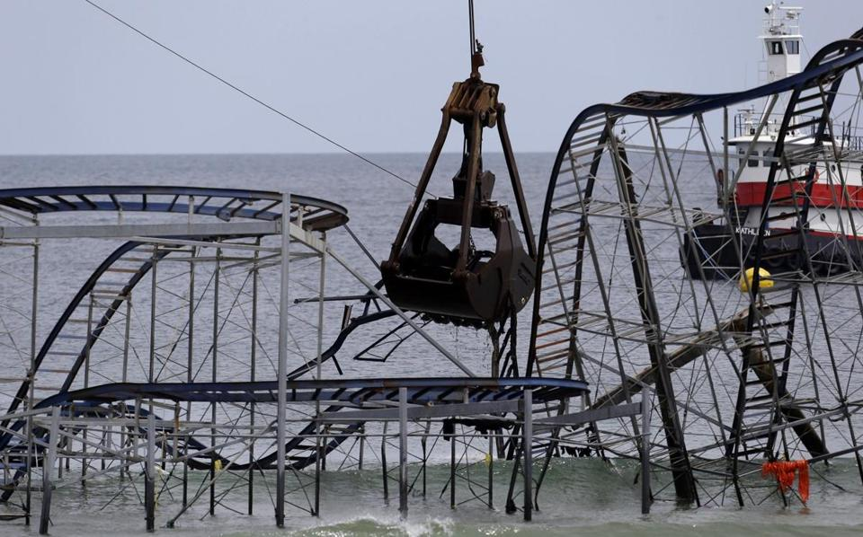 The claw of a crane tore through the structure of the Jet Star Roller Coaster Tuesday off the New Jersey coast. When Superstorm Sandy hit, the roller coaster plunged into the waves from an amusement pier where it had stood for decades.