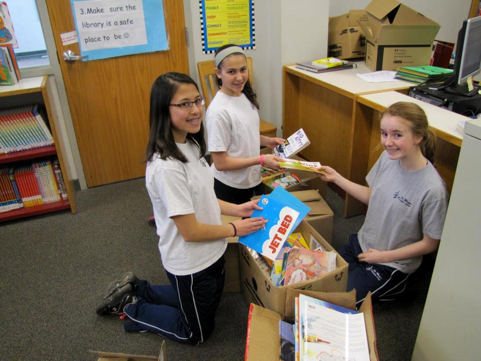 Angela Corkery, Sofia Pelletiere, and Grace Crowley sorted books bound for Ghana at St. Mary's Catholic School in Mansfield.