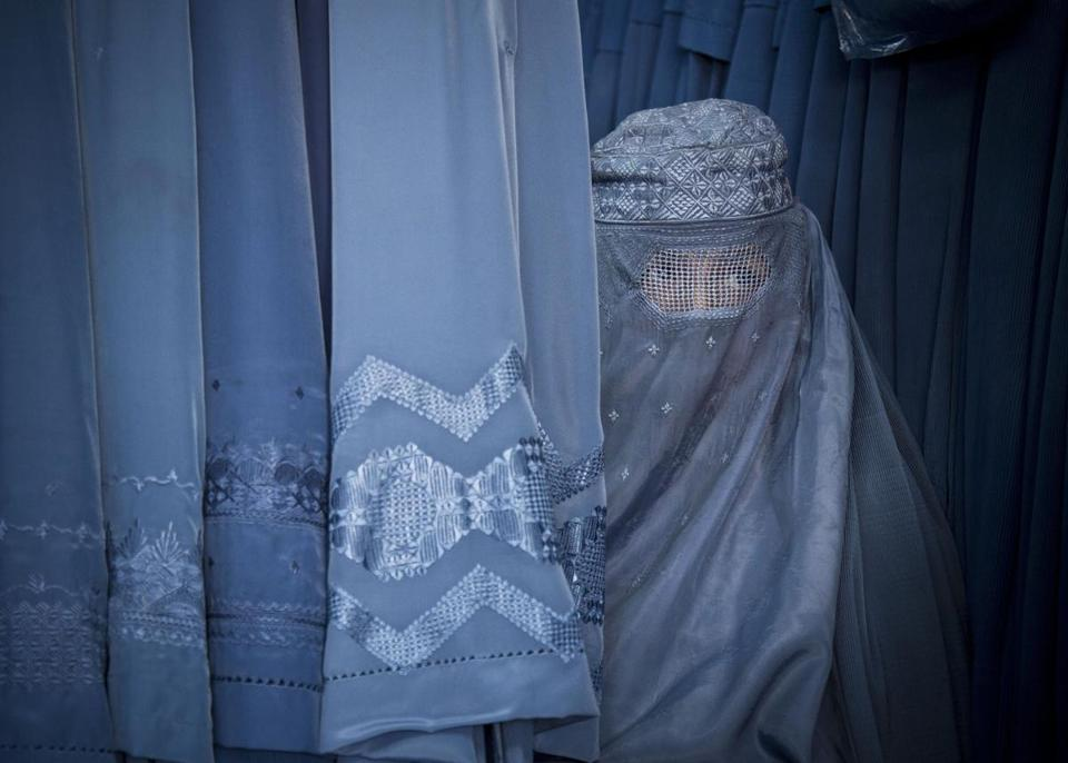 An Afghan woman peered through the eye opening of her burka as she waited to try on a new one in a shop in Kabul. Women have few protections under the law.