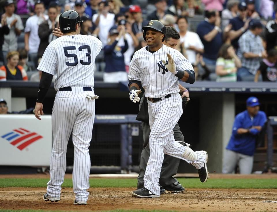 The Yankees' Robinson Cano is greeted at home plate by Austin Romine after hitting his second two-run homer of the game.