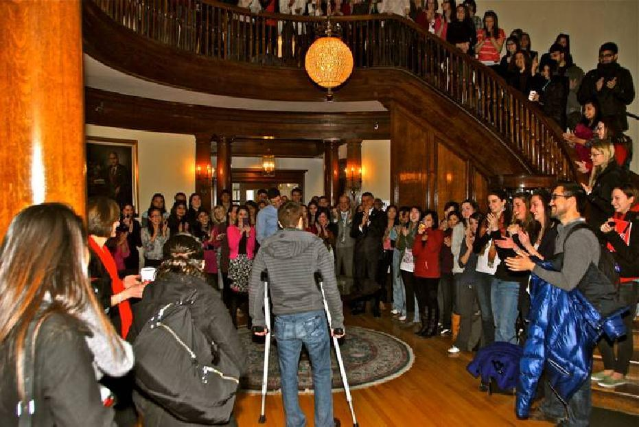 Nick Jones, on crutches, is welcomed back to the New England College of Optometry on Valentine's Day 2012 by his classmates, teachers and administrators at the Back Bay school.