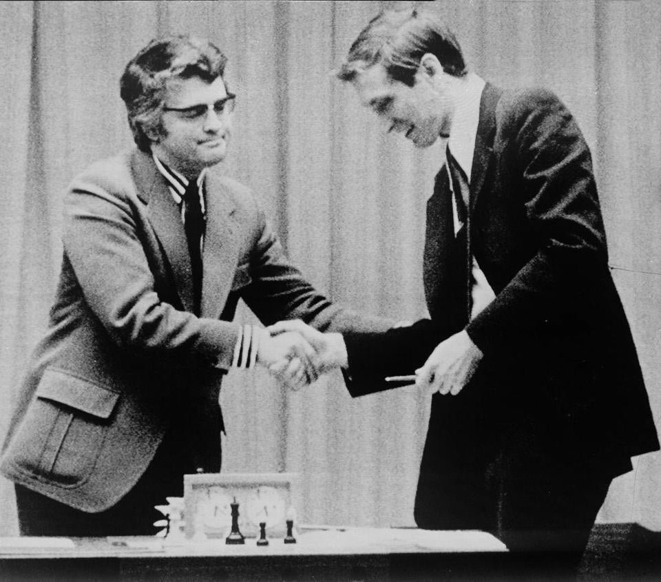 Bobby Fischer (right) shook hands with the chief referee of the World Chess Championship after learning that his opponent, Boris Spassky, resigned from the match.