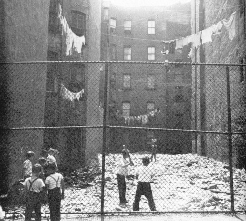 New York City children play stickball in a fenced-in back lot on the Lower East Side in 1951.