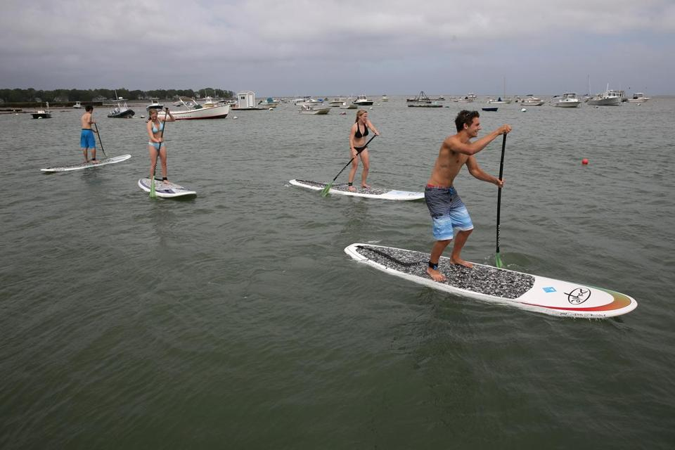 Stand-up paddleboarders at the Duxbury Bay Maritime School try out their water legs.