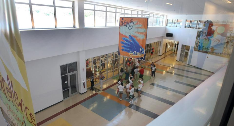 Occupancy sensors automatically switch off lights in classrooms at Newton North High, but none were installed in halls.