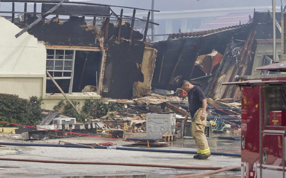A firefighter walked through what was left of the Southwest Inn, along a Houston expressway, following a deadly blaze.