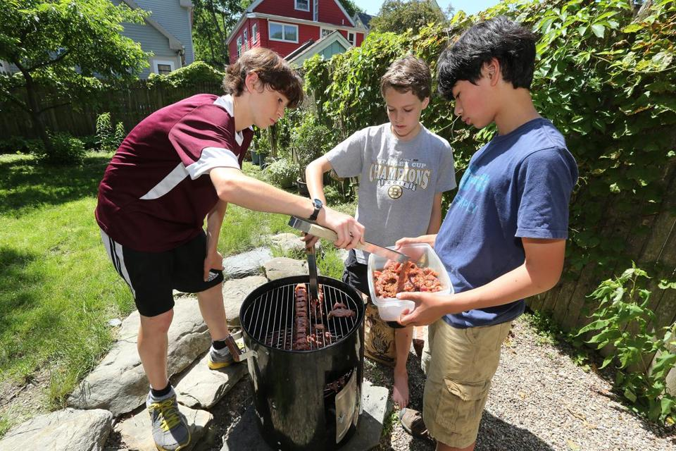 From left: Dante Greco-Henderson, Cooper Ducharme, and Caleb Mitchell smoking flank steak pieces that are marinated in brown sugar, soy sauce, ginger, and sesame oil.