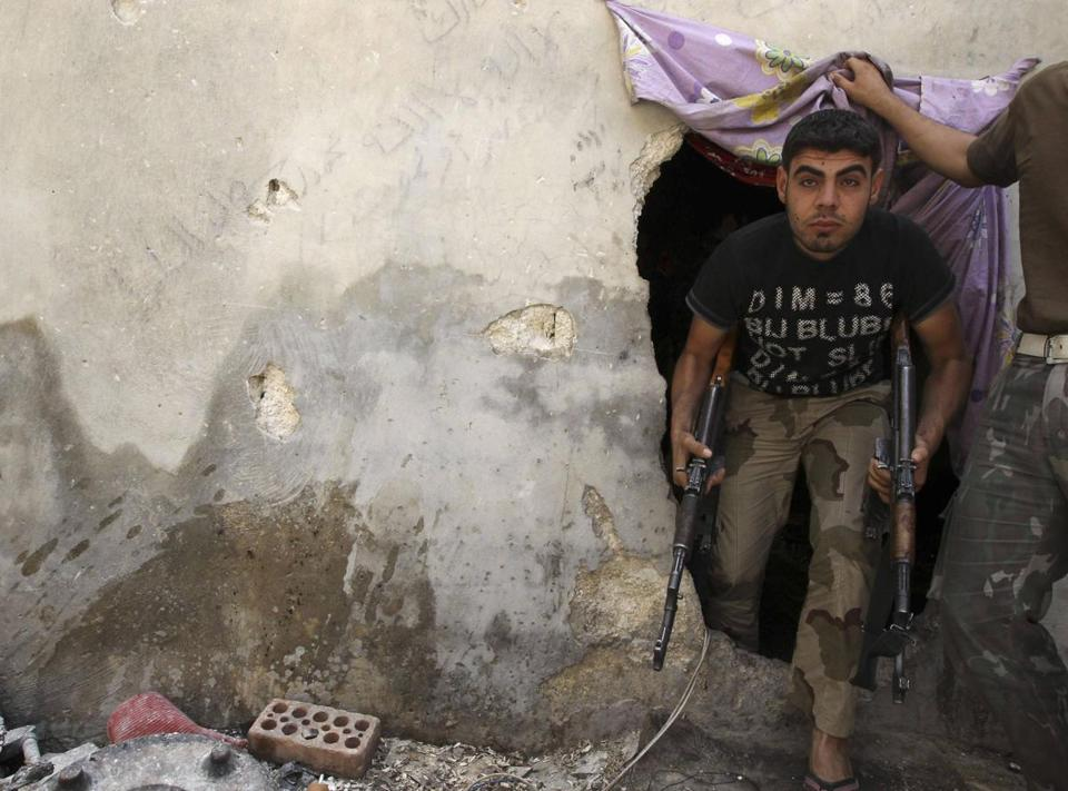 A Free Syrian Army fighter carried weapons as he emerged from a hole in a wall in Aleppo's Karm al-Jabal district Sunday.