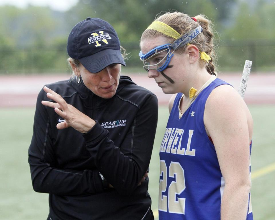 Norwell High girls' lacrosse coach Kara Connerty gives instruction to team captain Mary O'Connell during the Division 2 state lacrosse finals against Winchester, which Norwell won, 20-8, to claim its fifth lacrosse crown since 2005.