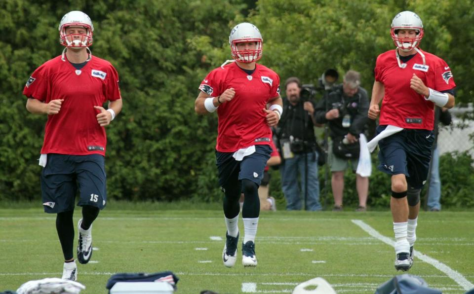 Tim Tebow, center, runs drills at a Patriots workout today between Ryan Mallett, left, and Tom Brady.
