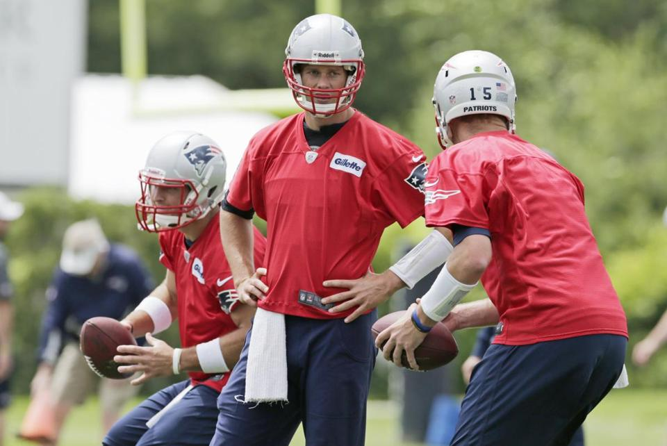 Tom Brady (middle) subscribes to coach Bill Belichick's philosophy on the importance of spring workouts.