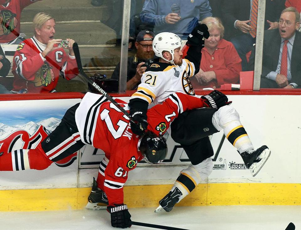 Andrew Ference, who played more than 45 minutes, fights to get past the Hawks' Michael Frolik.