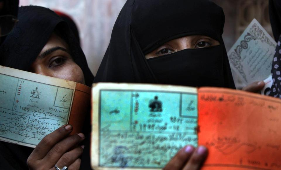 Iranian women showed their identity documents as they cast their ballots at the Iranian consulate in Karachi, Pakistan.