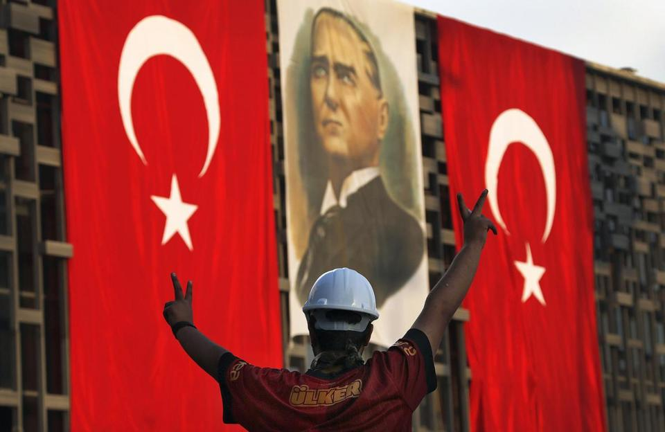 A protestor gestured before a portrait of former President Mustafa Kemal Ataturk in Instanbul's Taksim square.