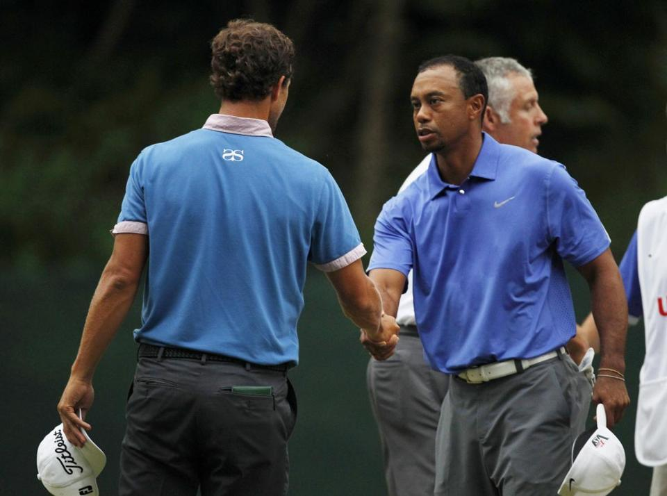 Tiger Woods (right) shakes hands with Adam Scott after their first day at the US Open was ended on No. 11.