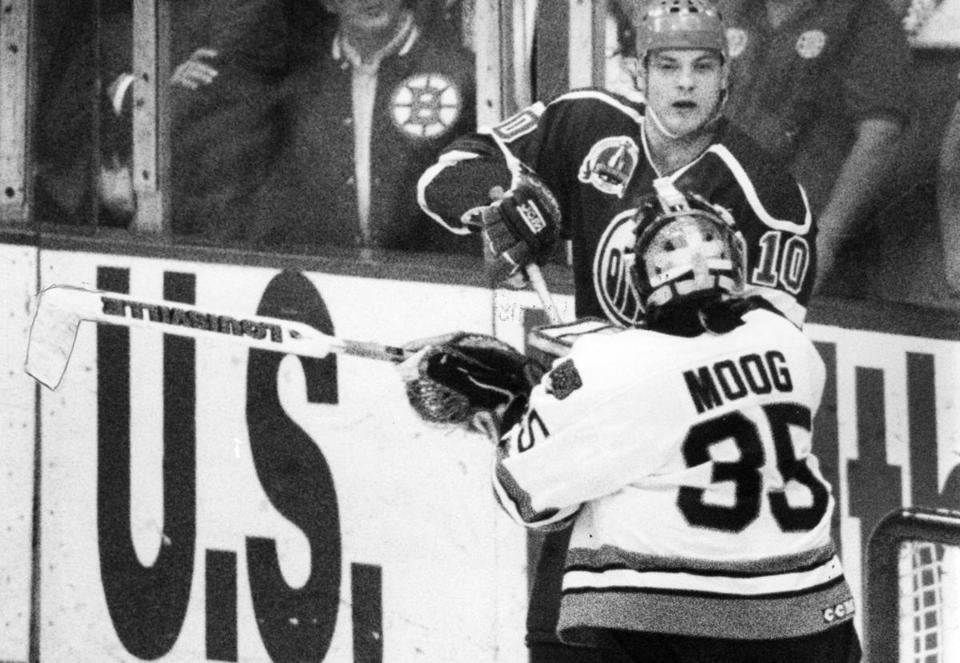Bruins goalie Andy Moog swings his stick at Esa Tikkanen of the Oilers during the Stanley Cup Final in 1990.