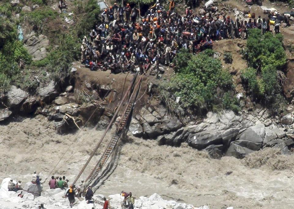 Indo-Tibetan Border Police (ITBP) personnel, in uniform, help stranded pilgrims on a makeshift bridge cross a stream of gushing floodwater in the northern Indian state of Uttarakhand, India.