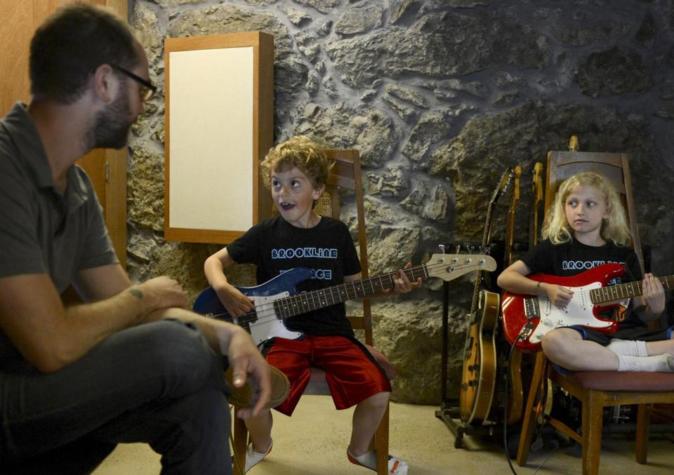 In his home studio in Jamaica Plain, Mike Irwin instructs members of the band the Brookline Village People: 8-year-old bassist Stefan Gordon and 7-year-old guitarist Catherine Macenka.