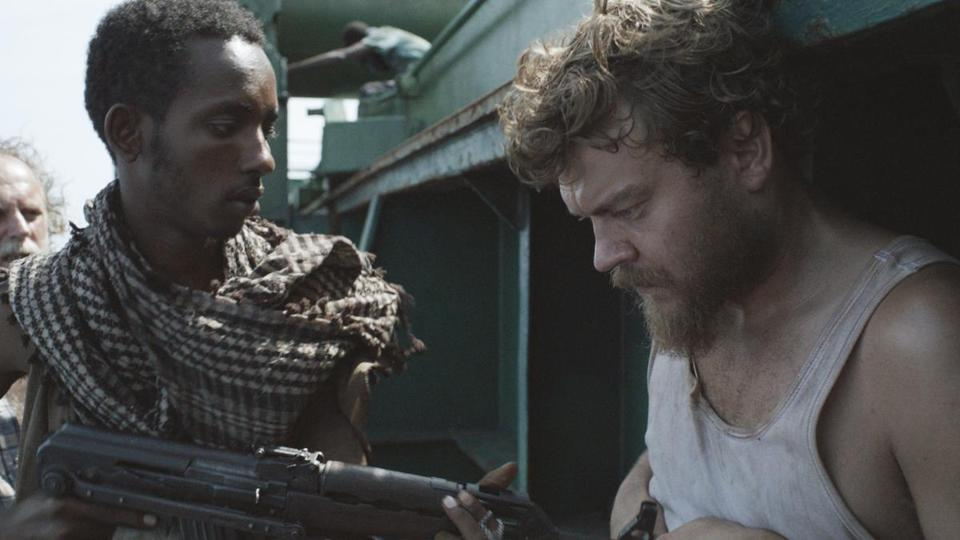 "Pilou Asbaek (second from left) acts as liaison between Abdihakin Asgar (left) and Soren Malling (right) in ""A Hijacking."""