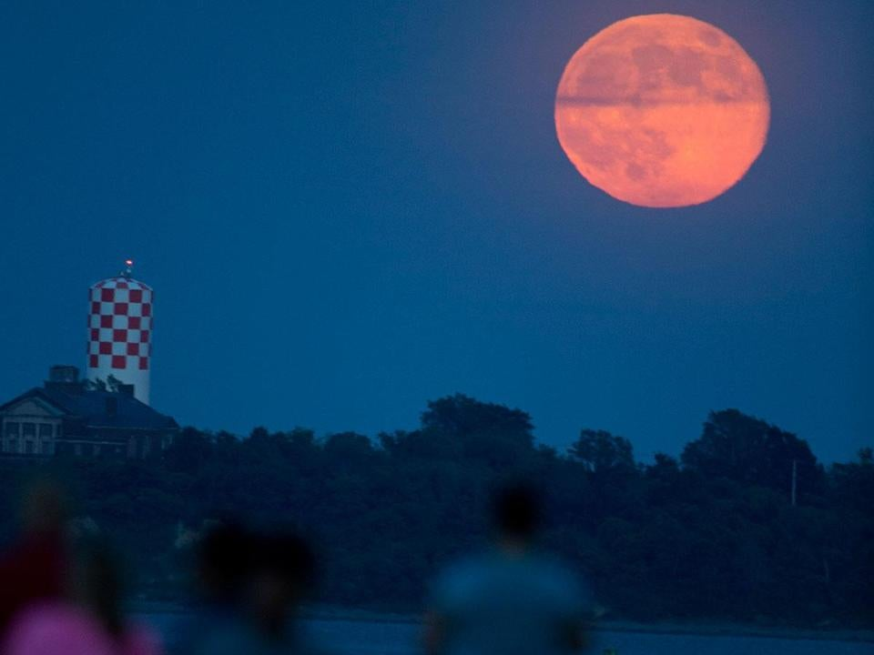 The supermoon, shown rising behind Long Island, was photographed from Castle Island before clouds covered the view.