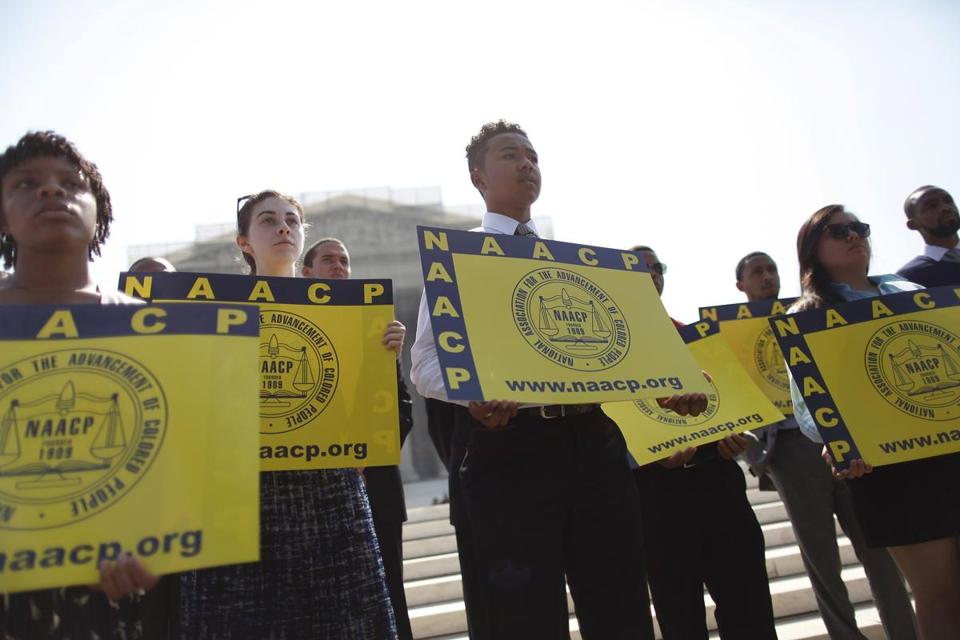 Interns from the NAACP held signs as civil rights experts spoke to reporters after the US Supreme Court struck down part of the Voting Rights Act.