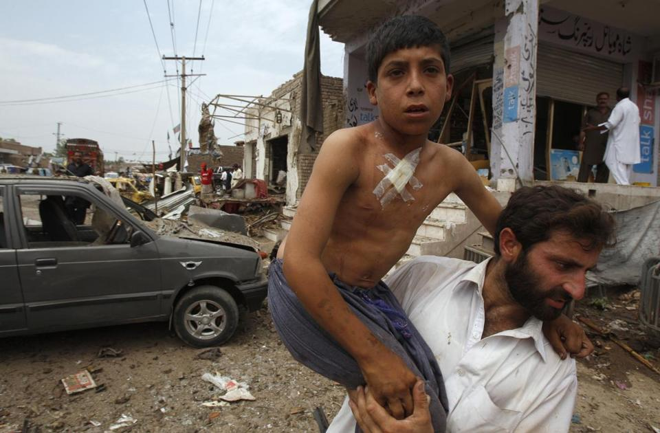 A Pakistani helped an injured boy at the site of a car bombing on the outskirts of Peshawar Sunday.