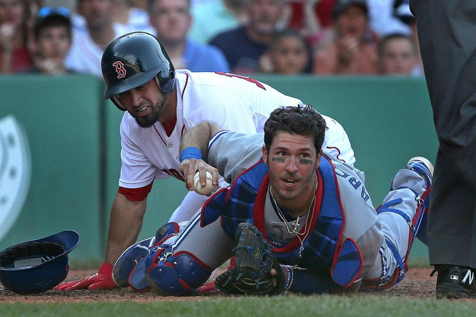 Toronto catcher J.P. Arencibia makes sure the umpire knows he has the ball after a collision at home plate in which Shane Victorino was called out.