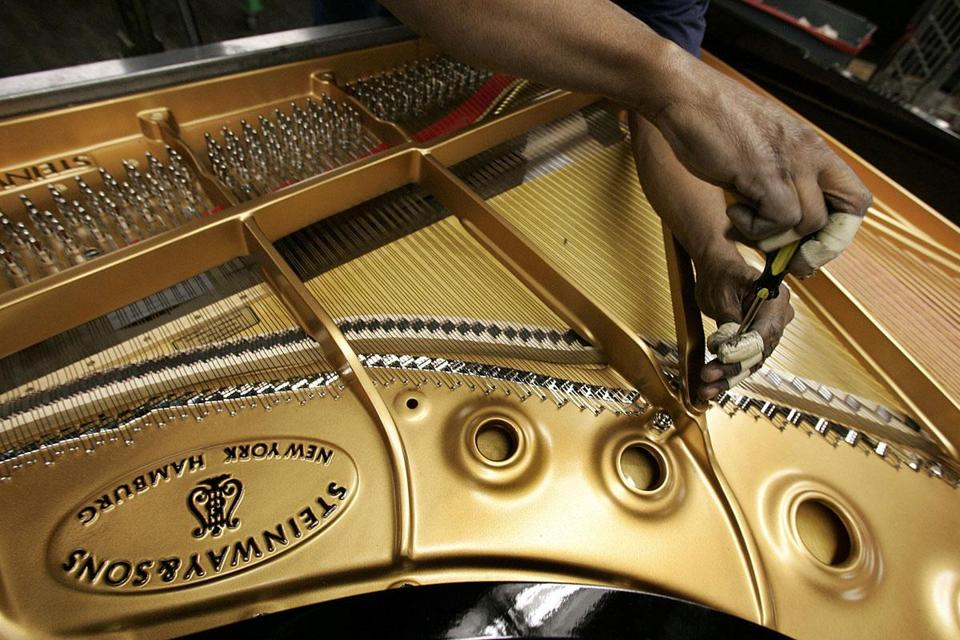 A worker tuned the soundboard of a Concert Grand Model D at a Steinway piano factory in Long Island City, N.Y.